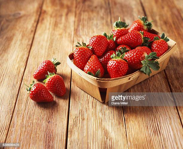 Punnet of strawberries on wooden table