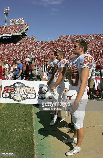 Punt kickers Ryan Bailey and Greg Johnson of the Texas Longhorns stand at attention during the national anthem before the Red River Shootout against...