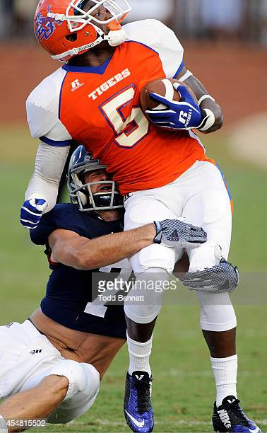 Punt returner Cantrell Frazier of the Savannah State Tigers is brought down by safety Matt Dobson of the Georgia Southern Eagles during the first...