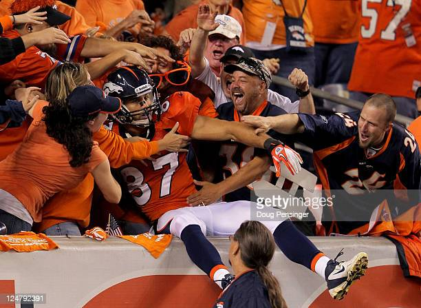 Punt returner Eric Decker of the Denver Broncos jumps into the stands after returning a punt 90yards for a touchdown in the third quarter against the...