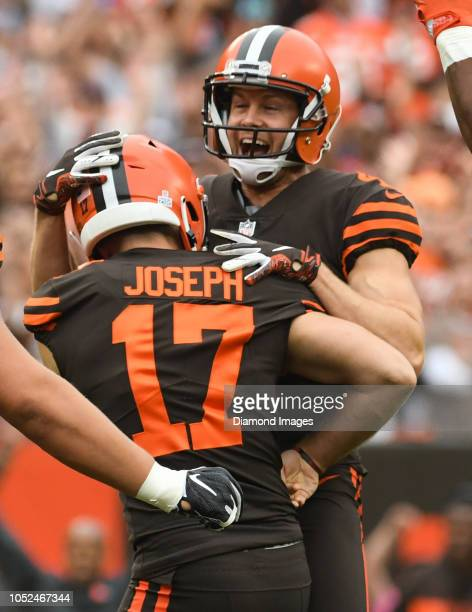 Punter Britton Colquitt of the Cleveland Browns embraces kicker Greg Joseph after Joseph kicked the game winning field goal in overtime of a game...