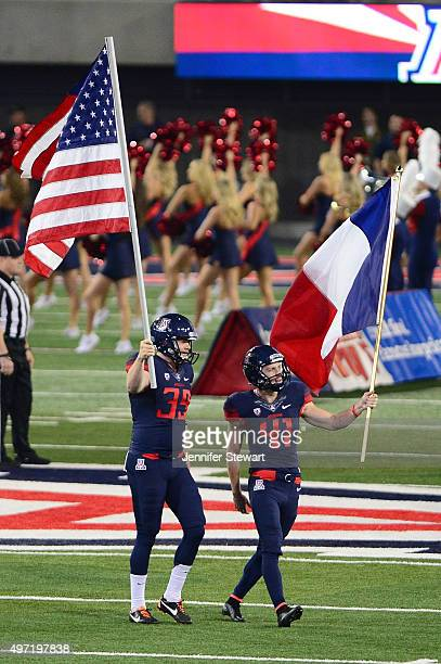 Punter Drew Riggleman and place kicker Casey Skowron of the Arizona Wildcats carry out the American and French flag prior to the game against the...