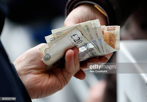 A punter passes over money to a bookmaker at Sandown racecourse on April 22 2016 in Esher England