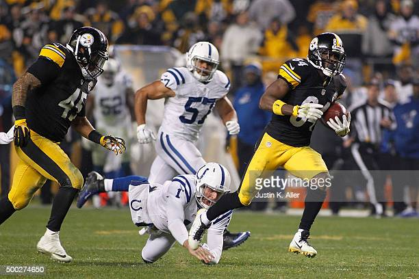 Punter Pat McAfee of the Indianapolis Colts attempts to tackle Antonio Brown of the Pittsburgh Steelers as he returns a punt for a 71 yard touchdown...