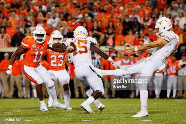 Punter Ryan Bujcevski of the Texas Longhorns kicks the ball away for 43yards against linebacker Amen Ogbongbemiga and safety Tre Sterling of the...