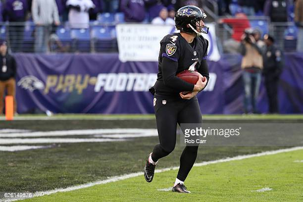 Punter Sam Koch of the Baltimore Ravens holds the ball for a safety against the Cincinnati Bengals in the fourth quarter at MT Bank Stadium on...
