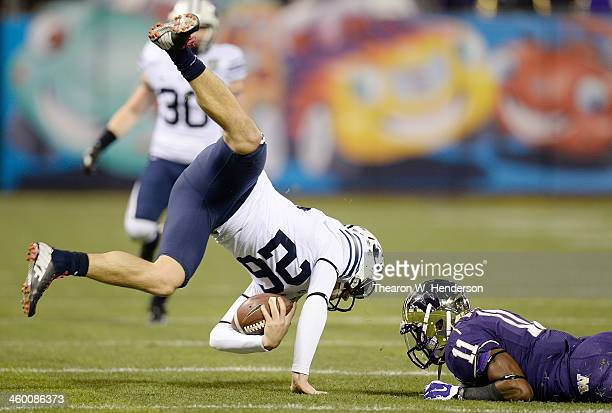 Punter Scott Arellano of the BYU Cougars gets tripped up short of the first down by Elijah Qualls of the Washington Huskies during the first quarter...