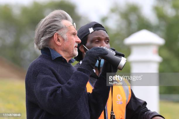 A punter uses his binoculars on Epsom Downs south of London on July 4 2020 to witness the 241st Epsom Derby which was postponed on June 6th and was...
