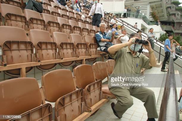 A punter watching a race with his binoculars on the podium of Sha Tin Racecourse A low attendance of punters was recorded on the racing day in Sha...