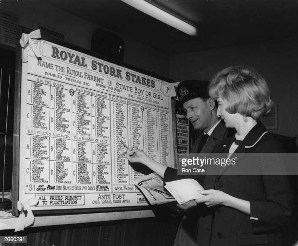 Punters examining the elaborate and well designed board for possible names for royal babies in England