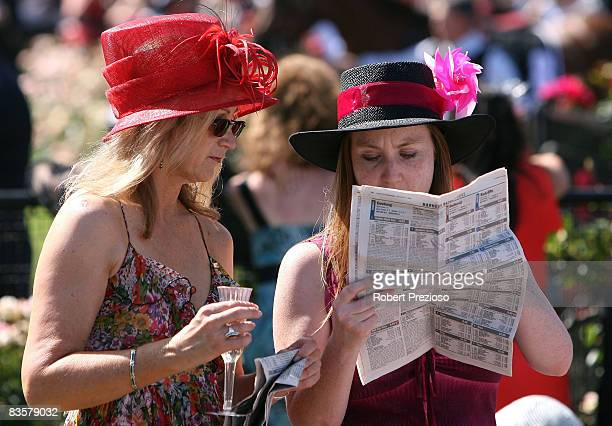 Punters look at the form guide during the 2008 Crown Oaks Day meeting at Flemington Racecourse on November 6 2008 in Melbourne Australia