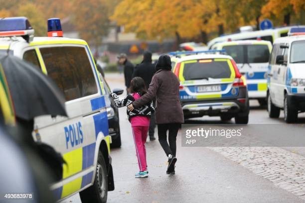 A pupil and her parent leaves a primary and middle school in Trollhattan southwestern Sweden on October 22 where a masked man armed with a sword...
