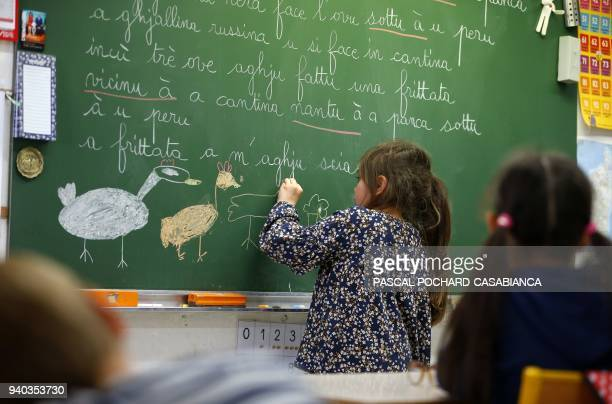 A pupil draws on a blackboard during a corsican language course in SaintJoseph school on March 30 2018 in Ajaccio on the French Mediterranean island...