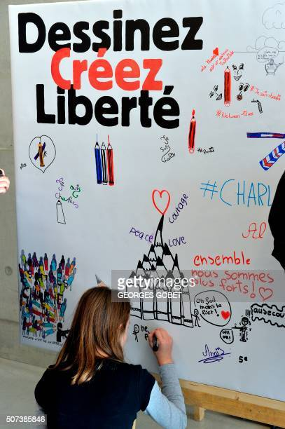 A pupil draws on a giant paper at a multimedia library in Angouleme on January 29 on the sideline of the city's Comics festival Charlie Hebdo...