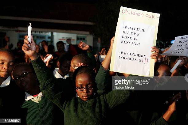 Pupil from Moi Nyeri Complex lifts up her hands during prayers and tributes for the Westgate Terror attack victims on September 27, 2013 outside...