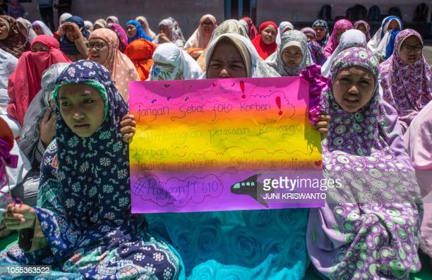 TOPSHOT A pupil holds up a placard calling for social media users to refrain from spreading graphic images of Lion Air flight JT 610 victims as...