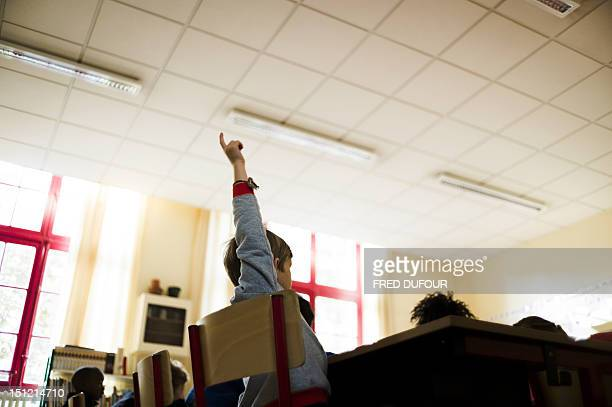 Pupil holds up his arm to ask a question at an elementary school on September 4, 2012 in Paris, after the start of the new school year. AFP PHOTO /...