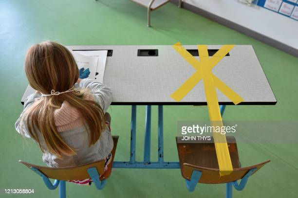TOPSHOT A pupil of the SainteCroix elementary school works as half of her writing desk is marked with a tape to ensure that safe distance is kept on...