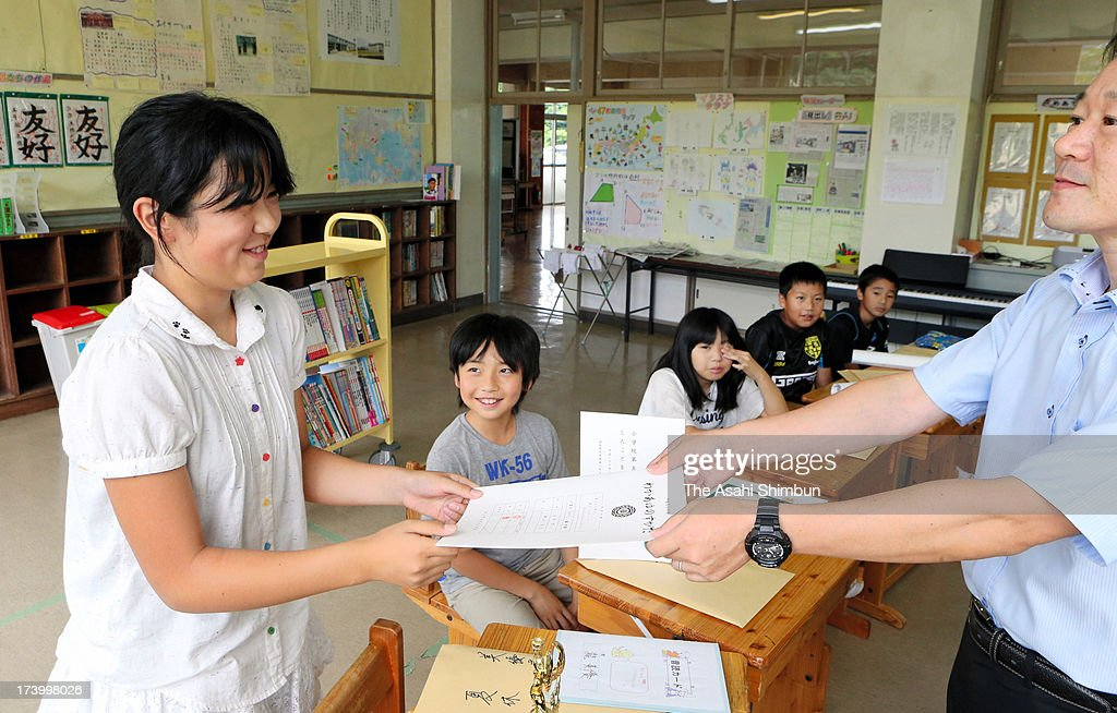 A pupil receives a report card at evacuated Namie Elementary School on July 19, 2013 in Nihonmatsu, Fukushima, Japan. The whole school has been evacuated from Namie town, where the school is only 9 kilometers from crippled Fukushima Daiichi Nuclear Power Plant. The school had no newcomers this year, only 19 pupils are studying, most of them are commuting from temporary housing.