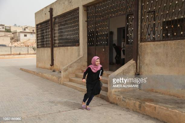 A pupil runs as she leaves her school in the city of Harim in the rebelheld northern countryside of Syria's Idlib province on October 15 2018 The...