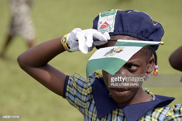 A pupil salutes as she holds a green and white Nigerian flag on October 1 2015 as part of Nigeria's independence anniversary celebrations in Lagos...