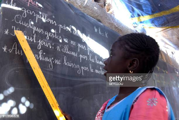 A pupil stands in front of the black board during class in a makeshift shelter used for the pilot primary school of the Global Partnership for...
