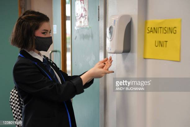 A pupil uses a sanitising unit as students return to Holyrood Secondary School in Glasgow for the first time following the easing of coronavirus...