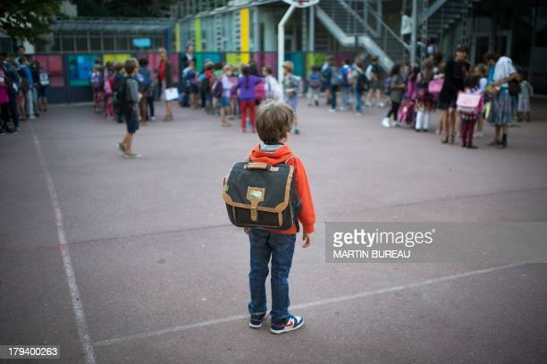 A pupil waits in the courtyard of a primary school on September 3 2013 in Paris on the first day of school More than 12 million pupils went back to...