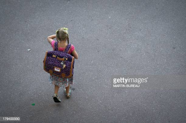 A pupil walks in the courtyard of a primary school on September 3 2013 in Paris on the first day of school More than 12 million pupils went back to...
