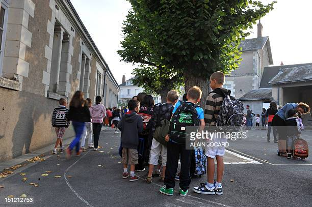 Pupils arrive with their parents at a primary school on September 4 2012 for an early start of the new school year in Francueil near Tours centre...