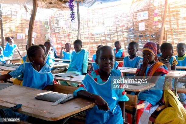 Pupils attend a class in a makeshift shelter used for the pilot primary school of the Global Partnership for Education in Tivaouane near Dakar on...
