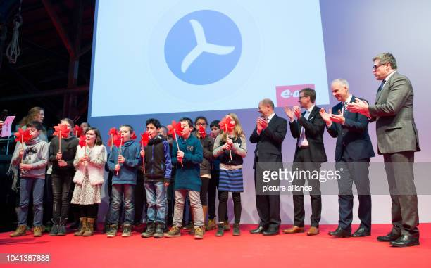 Pupils blow into small wind turbines as they stand next to Joerg Singer mayor of Helgoland municipality EON SE CEO Johannes Teyssen and Hamburg's...