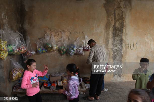 Pupils buy sweets in the courtyard of their school in the city of Harim in the rebelheld northern countryside of Syria's Idlib province on October 15...