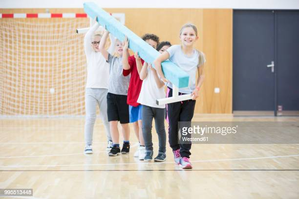 pupils carrying balance beam in gym class - school gymnastics stock photos and pictures