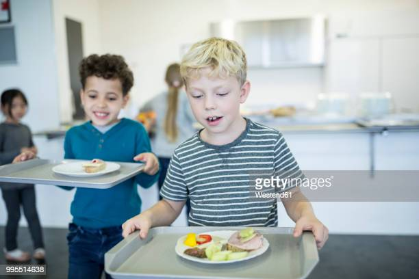 pupils carrying trays in school canteen - cantine photos et images de collection