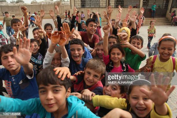 Pupils cheer in the courtyard of their school in the city of Harim in the rebelheld northern countryside of Syria's Idlib province on October 15 2018...