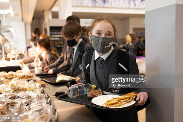Pupils collect lunch in the canteen on their first day back from lockdown at Chertsey High School on March 09, 2021 in Chertsey, United Kingdom....