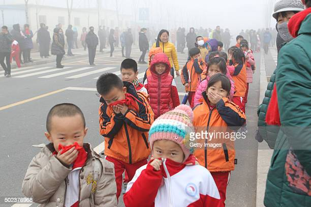 Pupils cover their noses after school in heavy smog on December 23 2015 in Binzhou China According to the Ministry of Environmental Protection of the...