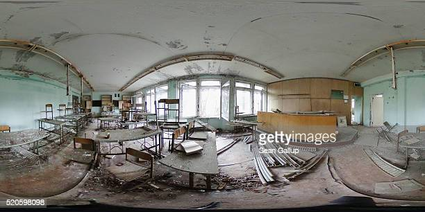 Pupils' desks and chairs stand scattered in a former classroom in elementary school number three on April 9 2016 in Pripyat Ukraine Pripyat built in...