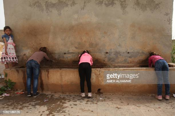 Pupils drink water from a fountain in the courtyard of their school in the city of Harim in the rebelheld northern countryside of Syria's Idlib...