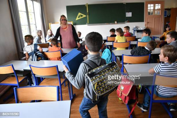 Pupils enter a classroom on the first day of school at the La Courbe primary school in Aytre western France on September 4 2017 / AFP PHOTO / XAVIER...