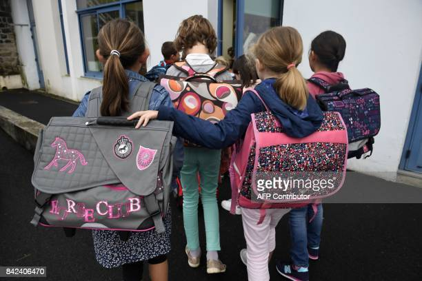 Pupils enter their classroom in a primary school on the first day of the new school year on September 4 in Quimper western France / AFP PHOTO / FRED...