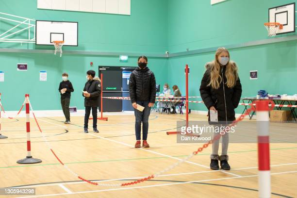 Pupils from Chertsey High School queue up to take lateral flow tests for Covid-19 ahead of their full return to school, on March 08, 2021 in...