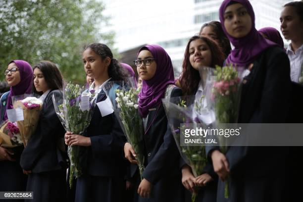 Pupils from Eden Girls' School in Walthamstow holds flowers at Potters Fields Park in London on June 5 during a vigil to commemorate the victims of...