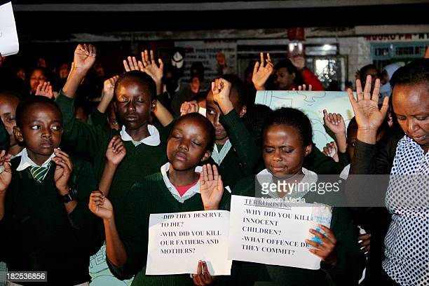 Pupils from Moi Nyeri Complex lift up their hands during prayers and tributes for the Westgate Terror attack victims on September 27 2013 outside...