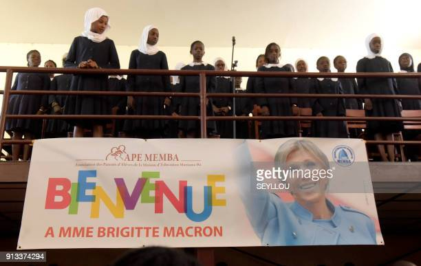 Pupils gather above a banner bearing the picture of the wife of French President Brigitte Macron displayed at Mariama Bash school on the island of...