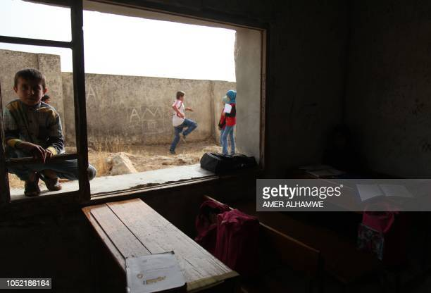 Pupils gather in front of a classroom at a school in the city of Harim in the rebelheld northern countryside of Syria's Idlib province on October 15...
