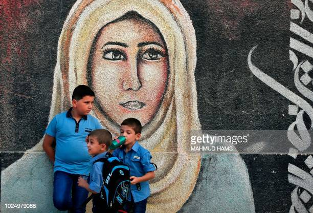 Pupils gather in front of a mural painting on their way to a school run by the United Nations Agency for Palestinian Refugees in Gaza City on August...