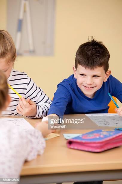 Pupils handing over slip of paper in classroom