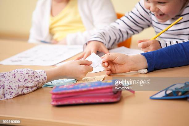 pupils handing over slip of paper in classroom - love letter stock photos and pictures